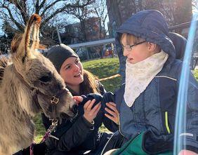 Ein Kind im Rollstuhl streichelt einen Esel